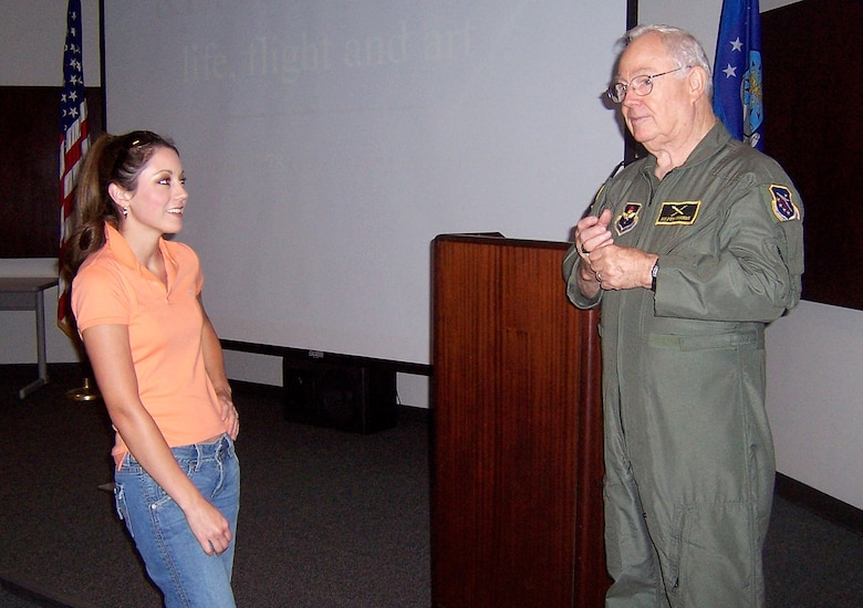 Mr. Keith Ferris, Air Force aviation artist, discusses his art techniques with Jana Hudson, wife of Capt. Dustin Hudson, 37th Flying Training Squadron Instructor Pilot, Thursday during a briefing in the Phillips Auditorium. (U.S. Air Force Photo by Sonic Johnson)
