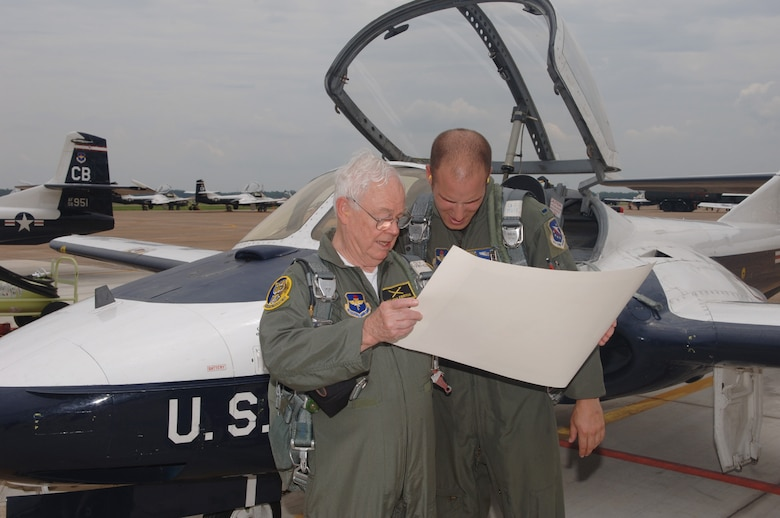 Mr. Keith Ferris, Air Force aviation artist, presents 1st Lt. Timothy Grebs, 37th Flying Training Squadron Instructor Pilot, with a lithograph of the old T-37 paint scheme. (U.S. Air Force Photo by Kenn Brown)