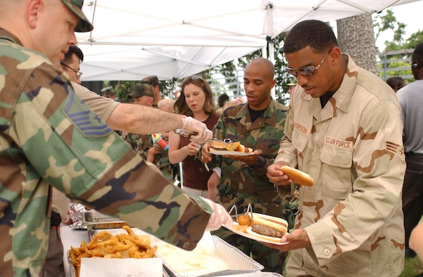 Master Sgt. Sherman Miller, 81st Security Forces Squadron, left, and Paul LaRive, 81st Mission Support Squadron, serve fried fish to Senior Airmen Stephanie Brown, 81st Medical Support Squadron, Nathaniel Sheppard 81st MDSS and Robert Anderson, 81st Comptroller Squadron at the welcome home picnic for Airmen recently returned from deployments  at marina park June 22.  Airmen Sheppard and Anderson were deployed to Kuwait from January to May and Airman Brown was deployed to Qatar from January to May.  (U. S. Air Force photo by Kemberly Groue)
