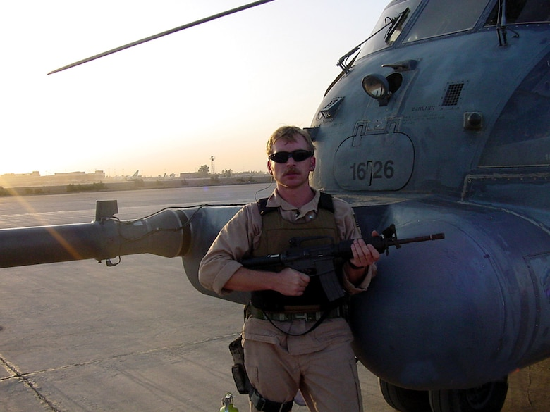 Tech. Sgt. Christian MacKenzie poses stands next to an Air Force special operations MH-53 Pave Low helicopter July 12, 2003, at Baghdad International Airport. Sergeant MacKenzie served as a flight engineer on the helicopter and flew low-level, long-range, undetected missions into enemy territory, day or night, in all kinds of weather, to insert, extract and resupply special operations forces. (Courtesy photo)