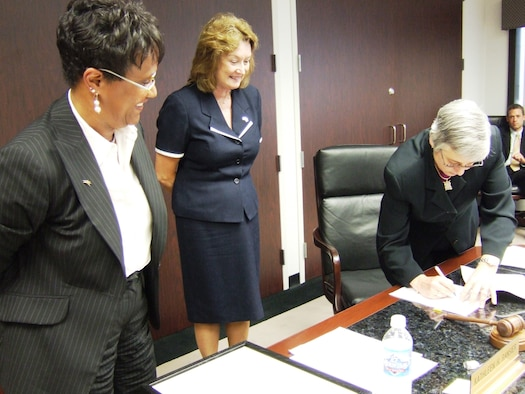 Columbus Regional Airports Authority Board of Directors Chairwoman Kathleen H. Ransier (left) and Air Force Real Property Agency Director Katie Halvorson (center) watch as CRAA President and Chief Executive Officer Elaine Roberts signs the deed for the final parcel of property at the former Rickenbacker Air National Guard Base, Ohio June 26. (Photo courtesy of the Columbus Regional Airports Authority)