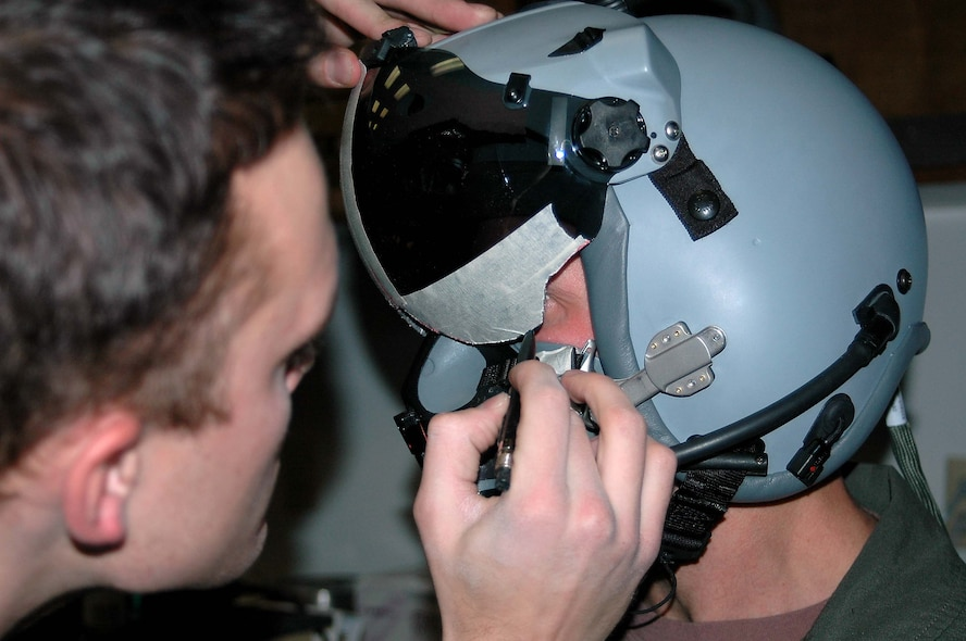 Capt. Lee Dewald, 4th Fighter Squadron pilot, gets an individual fit for his new helmet to fly with the CCIP jets. Senior Airman Mark Fredrickson pencils in around the edges to accurately measure where the visor should be shaved off in order to get a perfict fit.