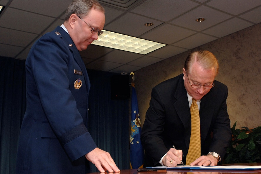 Maj. Gen. Kevin Sullivan, Ogden Air Logistics Center commander, watches as Dr. Richard Kendell, with the commission for the Utah System of Higher Education, takes his turn signing the Education and Training Alliance memorandum here Monday.
