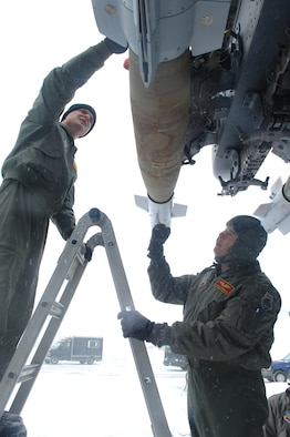 MINOT AIR FORCE BASE, N.D. -- First Lt. Justin Cox (left) and Capt. Dennis Cummings, both from the 23rd Bomb Squadron, inspect a laser guided bomb attached to a B-52H Stratofortress before a scheduled flight Feb. 28, 2007. Snow fall accumulation delayed the flight until March. 1. The crew will fly to the Marine Corps Air Ground Combat Center 29 Palms, Calif. to test the missile. (U.S. Air Force photo by Senior Airman Christopher Boitz)