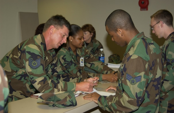 Tech. Sgt. David Wilder, 325th Mission Support Squadron base training manager, reviews an Airman's training folder in a mass deployment line during the Operational Readiness Inspection in 2005.