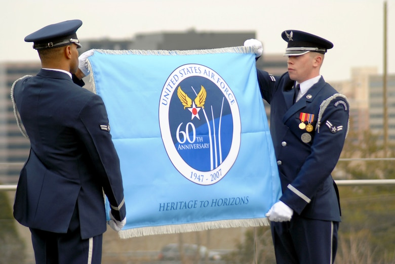 Airmen 1st Class Ahmad Ware (left) and Brandon Bridges unveil the Air Force 60th Anniversary flag for the first time March 1 at the Air Force Memorial in Arlington, Va.  The ceremony was attended by Chief of Staff of the Air Force Gen. T. Michael Moseley and Secretary of the Air Force Michael W. Wynn.   The Airmen are Air Force Honor Guard ceremonial guardsmen.  (U.S. Air Force photo/SSgt. Madelyn Waychoff)