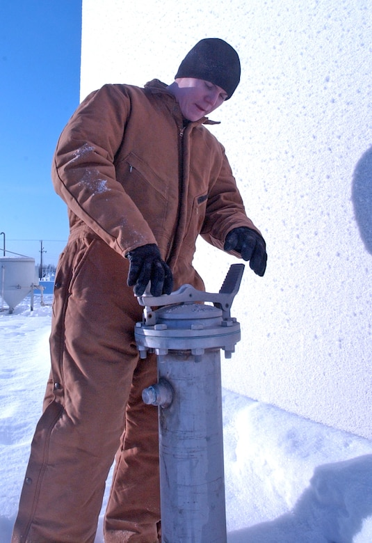 "EIELSON AIR FORCE, Alaska -- Staff Sgt. Kyle Evans, 354th Logistics Squadron, inspecs a ""Tell Tale"" pipe used to detect any leaks under a bulk fuels storage tank. Working at the farthest-north Air Force base in the world - located 150 miles south of the Arctic Circle - presents these Airmen with challenges some have never faced before. (U.S. Air Force photo by Senior Airman Justin Weaver)"