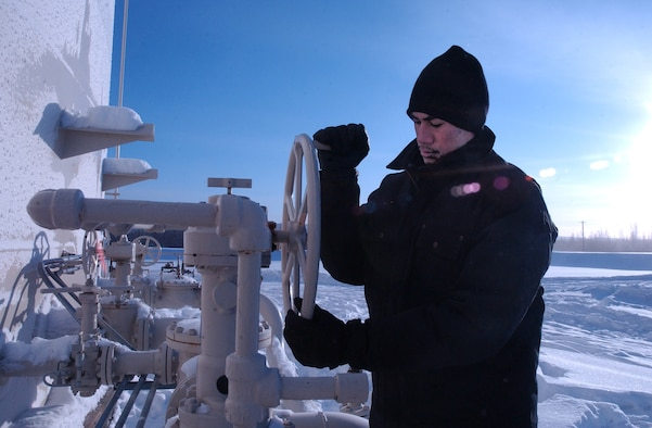 EIELSON AIR FORCE, Alaska -- Airman 1st Class Jeremiah Ulu, 354th Logistics Squadron facilities operator, inspects a fuels valve for leaks and ease of operation. Fighting temperatures as low as minus 60, Airman Ulu performs daily checks on each bulk fuels storage tank. (U.S. Air Force photo by Senior Airman Justin Weaver)