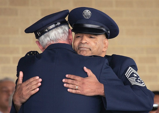 The retiring command chief master sergeant of Air Education and Training Command, Chief Master Sgt. Rodney E. Ellison, receives a heartfelt hug from Gen. William R. Looney III, AETC commander, while in the reviewing stands at the basic military training graduation parade March 2 on Lackland Air Force Base, Texas. (Air Force photo by Robbin Cresswell)