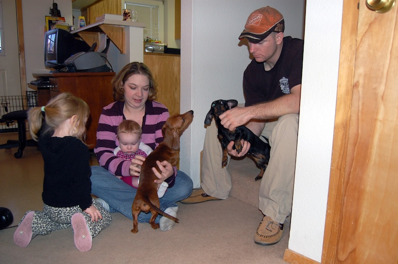Staff Sgt. Philip Bridges, his wife, Jamie (center), Liberty (left), and 8-month-old Lily, play with their dogs in their new home in base housing Feb. 27 at Eielson Air Force Base, Alaska. They were one of 300 families living in the Sprucewood Homes section of the base's privatized housing. The Bridges and other Air Force families had to be moved out of the privatized housing into new housing from September to December. The reason for the move was due to a conclusion of a privatized housing contract that wasn't able to be renegotiated. (U.S. Air Force photo/Staff Sgt. Matthew Rosine)
