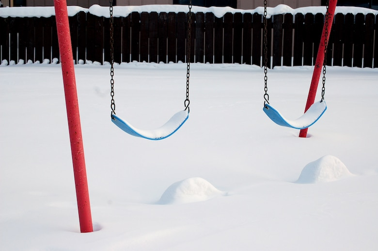 Abandoned swings sit covered in snow in the Sprucewood Homes section of base housing Feb. 27 at Eielson Air Force Base, Alaska. Three hundred Air Force families had to be moved out of the privatized housing into new housing from September to December. The reason for the move was due to a conclusion of a privatized housing contract that wasn't able to be renegotiated. (U.S. Air Force photo/Staff Sgt. Matthew Rosine)