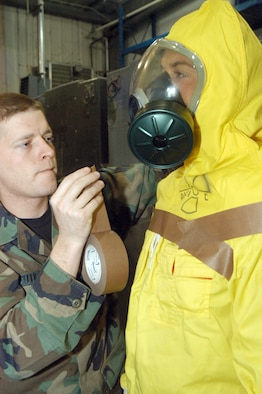 Senior Airman Chris Butler, a Readiness Flight readiness logistics journeyman, tapes loose edges of an anti-C (radiation suit) worn by Senior Airman Nick Pompa to minimize skin exposure. U.S. Air Force photo by Sue Sapp.
