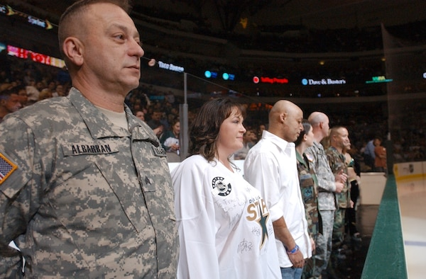 RANDOLPH AIR FORCE BASE, Texas - Sergeant Kenneth Albarran (left), a war veteran undergoing treatment at Brooke Army Medical Center, and several other San Antonio military members and veterans stand as they are recognized in between periods at a Dallas Stars hockey home game Feb. 23. (U.S. Air Force photo by Staff Sgt. Beth Del Vecchio)
