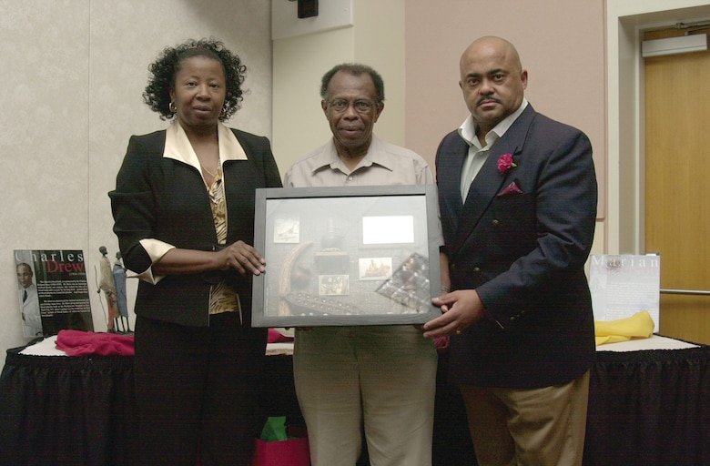 Karen Mitchell (left) and Master Sgt. David Bryan present Wendell Johnson (Center) with a gift as token of appreciation for Mr. Johnson's more than 40 years of service to Goodfellow and his extensive participation in the base's African-American Heritage Committee. (U.S. Air Force photo by Airman 1st Class Luis Loza Gutierrez)
