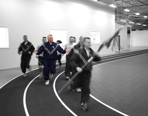 Members from the Northeast Air Defense Sector in Rome, N.Y., run for the first time during the NEADS Fitness Center opening Friday. The new fitness center was funded by First Air Force, and the new facility will house an indoor running track, basketball court, two racquetball courts, three saunas, an aerobics room and weight room.  Photo Illustration by Master Sgt. Carlos Castro
