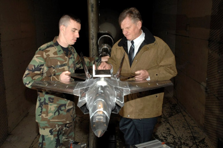 First Lt. Ezra Caplan and Charlie Smith examine a 12-percent scale model of the Navy variant of the F-35 Lightning II joint strike fighter during a break in the final pre-production aerodynamics testing done on all F-35 variants at Arnold Engineering Development Center, Arnold Air Force Base, Tenn.  Lieutenant Caplan is the AEDC Air Force project manager and Mr. Smith is the Aerospace Testing Alliance senior project engineer.  (U.S. Air Force photo/Rick Goodfriend)