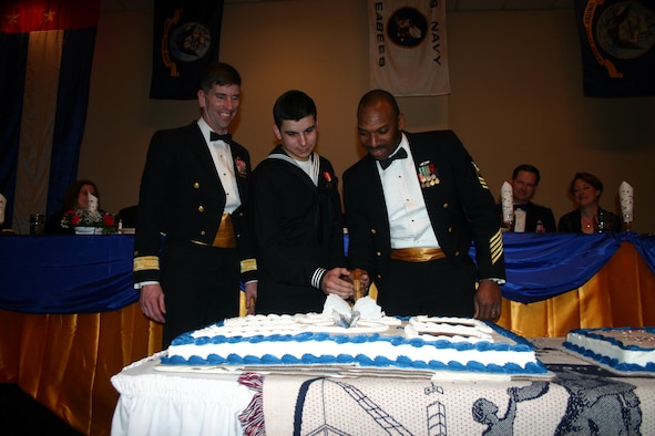Navy Rear Admiral Mark Handley observes as Seaman Alex Spears and Senior Chief Petty Officer Todd Bolden, the youngest and oldest Seabees in attendance, cut the cake during the Seabee Ball at the Howard Johnson Plaza Hotel March 3. (U.S. Air Force photo/Staff Sgt. Tonnette Thompson)