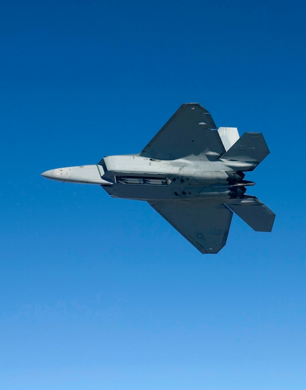 An F-22A Raptor flies Feb. 2, 2007, with four Small Diameter Bombs on board. Pilots and engineers from the F-22 Combined Test Force were performing load tests to ensure the GBU-39/B Small Diameter Bomb system does not exceed structural load boundaries for the Raptor. (Photo by Darin Russell)