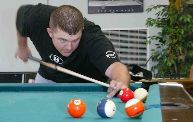 SHAW AIR FORCE BASE, S.C. -- Senior Airman Eric Charlton, 20th Civil Engineer Squadron Explosive Ordnance Disposal technician, performs a trick shot March 5 at the community center. Airman Charlton played the top players from all over the world and won 9th place as well as $500 at the National 9-Ball Bar Table Pool Tournament in Reno, Nev., from Feb. 28 to 30. Airman Charlton said 9th is the best he has ever placed in a national tournament. He competed against 145 people and won seven matches in a row to further himself to victory when he lost against Kim Davenport who plays on the U.S.A. pool team. (U.S. Air Force photo/Senior Airman John Gordinier)