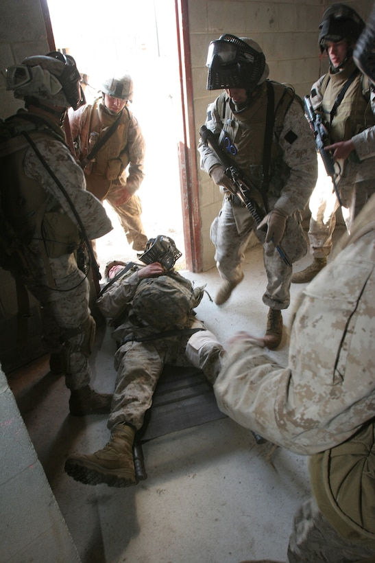 """Private First Class Lantz W. Atkins, a Greenville, SC, native lays motionless as a """"casualty"""" while his fellow Marines rush to provide him aid within a Casualty Collection Point during a raid training exercise aboard Camp Lejeune, NC, Mar. 6, 2007.  The Marines and sailors of Co. I will serve as the helicopter-borne assault company of BLT 3/8 and are scheduled to deploy as the Ground Combat Element for the 22d Marine Expeditionary Unit later this year.  (U.S. Marine Corps photo by Cpl. Peter R. Miller)"""