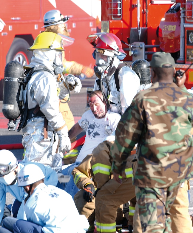 Kadena Air Base and Okinawan firefighters take and treat moch victims during the first bilateral off-base exercise Feb. 28, 2007, between Kadena Air Base emergency responders and local Okinawan police, fire and medical teams.  The exercise was conducted to enhance cooperation between base and off-base agencies in the event of an aircraft accident.