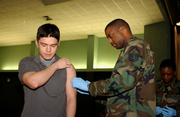 OSAN AIR BASE, Republic of Korea --  Master Sgt. Bruce Mckenzie (right) was one of many people from the 51st Medical Group vaccinating wing and 7th Air Force people at the base theater Wednesday and Thursday. (U.S. Air Force photo by Airman 1st Class Chad Strohmeyer)