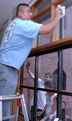 SUWON, Republic of Korea --  Staff Sgt. Caesar Alvarado, Detachment 2, 18th Intelligence Squadron, goes high while Staff Sgt. Marcus Harkins and Airman 1st Class Mi Kim, 303rd Intelligence Squadron, go low in cleaning a seemingly endless number of windows at the Little Sisters of the Poor home for Korean elderly in August. Volunteers do monthly chores such as washing windows, cleaning the kitchen, doing yard work, baking cookies, moving furniture and rebuilding damaged infrastructure.  (U.S. Air Force photo by Tech. Sgt. Michael O'Connor)