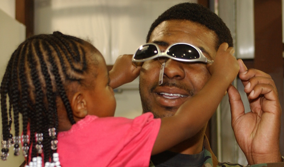 Three-year-old Taleeyah Perry, daughter of Staff Sgt. Joseph and Tamico Perry, helps her dad try on some sunglasses at the new Army and Air Force Exchange Service temporary mini-mart on T Street.  Sergeant Perry is assigned to the 85th Engineering Installation Squadron.  The $4,038,197 facility, which opened March 1, serves Keesler customers until a $40 million base exchange is completed late next year to replace the structure gutted by Hurricane Katrina 18 months ago.  Hours are 9 a.m. to 6 p.m. Monday-Saturday and 10 a.m. to 6 p.m. Sunday.  (U.S. Air Force photo by Kemberly Groue)