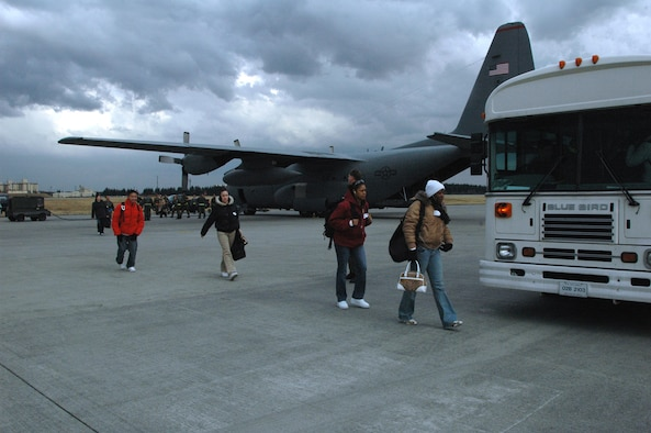 YOKOTA AIR BASE, Japan March 6, 2007 -- Members of the 8th Fighter Wing make their way from a C-130 to awaiting buses to inprocess at Yokota Air Base, Japan. The members, portraying non-combatants evacuating Korea, were part of the Wolf Pack?s NEO inspection March 6.