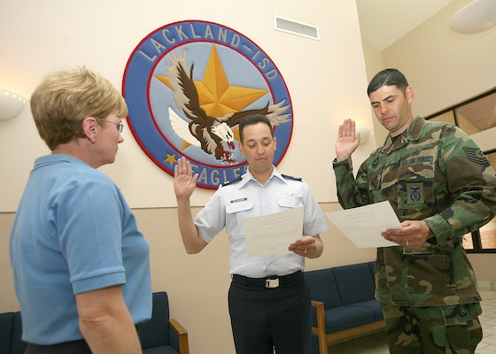 Capt. Angel Betancourt and Tech. Sgt. Luis Rivera, the two newest members of the Lackland Independent School District school board, take the oath of office Feb. 23 in front of Diana Watkins, the LISD administrative assistant. (USAF photo by Robbin Cresswell)