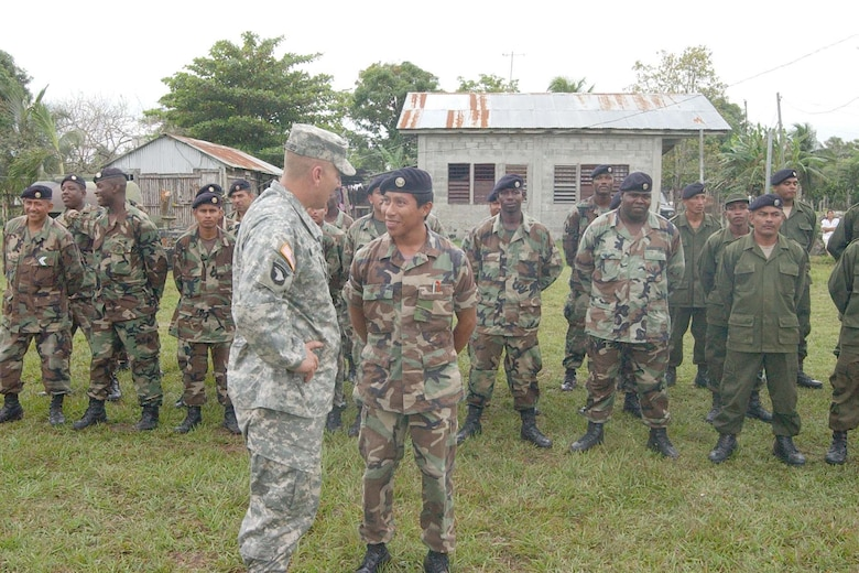 TRIAL FARM, Belize -- Army Col. Christopher Hughes, Joint Task Force-Bravo commander from Soto Cano Air Base, Honduras, talks with a member of the Belize Defense Force during the New Horizons Belize 2007 opening ceremonies. Active-duty and Guard Soldiers, Sailors and Airmen will work shoulder to shoulder with members of the Belize Defense Force during New Horizons Belize 2007.  (U.S. Air Force photo/Staff Sgt. Chyenne Griffin)