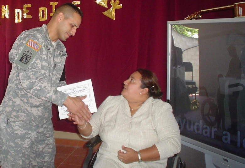 COMAYAGUA, Honduras -- U.S. Army 1st Lt. Hector Ayala, Joint Task Force Bravo's Joint Security Forces deputy commander, accepts a certificate of appreciation on behalf of the unit from Nellie Zelaya, director of Casayuda Foundation, during a ceremony March 8.  Casayuda Foundation, an orphanage and school for special needs children, celebrated its 8th anniversary and took a moment to recognize the men and women of JSF, who routinely provides support to them, spending time with the children, making repairs to the school's infrastructure and providing them with much-needed supplies. (U.S. Air Force photo/Capt. Alysia Harvey)