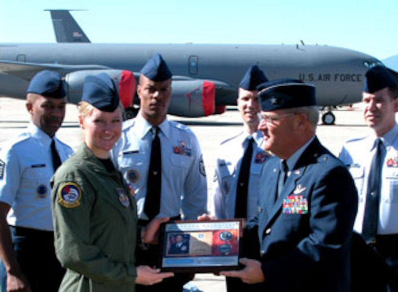 "Senior Airman Lyndsey Wisniewski, 452 AES, receives a plaque and coin from Brig. Gen. James Melin, 452 AMW commander, for her contribution to the Air Force Reserve ""Get One"" recruitment program. In addition, the award presentation was filmed by a production company which will use the footage to promote the Air Force Reserve. The program is open to all Air Force reservists, with the exception of AFRC Recruiters, their family members and Reserve liaisons. The Get One awards are primarily commemorative coins. For every referral submitted, the reservist receives a Referral Coin Award numbered one through ten, the number corresponding to the number of referrals. Accession coins are fashioned after commander's coins and are awarded to reservists when a referral turns into an accession. Coins are awarded from one through four accessions. The award for the fifth accession is a leather portfolio and pen and the sixth accession is a pair of pewter steins. For more information go to http://get1now.us (U.S. Air Force photos by Maj. Don Traud)"
