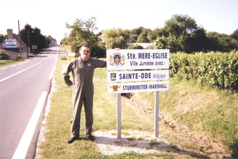 Senior Master Sgt. Jim Crawford stands by a sign at the Ste. Mare, France D-Day Commemorative Airdrops 50th anniversary. (Photo provided Jim Crawford)