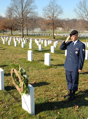Senior Airman Dustin Woodford, U.S. Air Force Honor Guard, salutes his fathers grave site at Arlington National Cemetery.