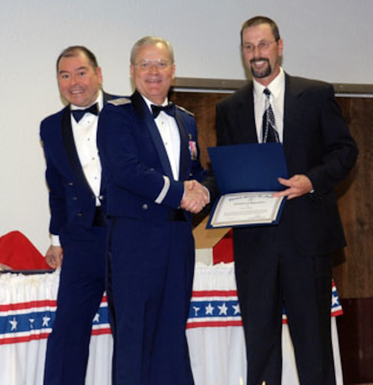 Brig. Gen. James L. Melin, 452nd AMW commander, presents the GS-07 through GS-11 Civilian of the Year award to Mr. Cary Kerr, 452 SVS.  Also congratulating Mr. Kerr is 452nd AMW Command Chief Master Sgt. Agustin Huerta, left.  The 452d Air Mobility Wing's 13th Annual Awards Banquet recognized the men and women in the wing who have made a difference in 2006.   The banquet was held at March Air Reserve Base in February.  (U.S. Air Force photo by 4th Combat Camera)