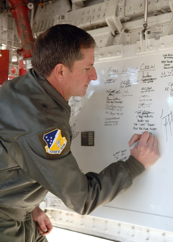 Brig. Gen. David Goldfein, 49th Fighter WIng commander, signs the bay door of one of the retiring F-117A Nighthawks. Six Nighthawks retired to Tonopah Test Range, Nev., March 12. (U.S. Air Force photo by Airman Jamal Sutter)