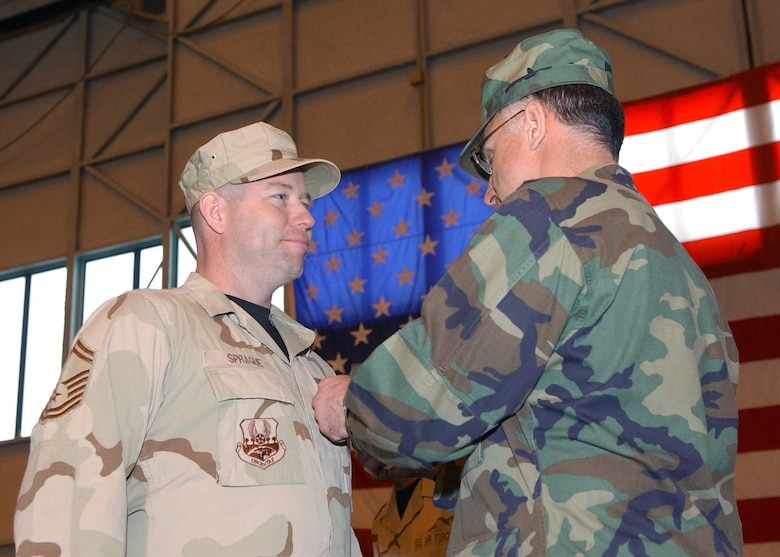 Senior Master Sgt. Dean Sprague, 354th Logistics Readiness Squadron, accepts the Soldier's Medal from 354th Fighter Wing Commander Brig. Gen. Dave Scott during a Welcome Home Ceremony for returning deployed airmen at Eielson Air Force Base, Alaska March 9.  Sergeant Sprague's heroic efforts saved the lives of five Afghan civilians during his deployment.  (U.S. Air Force Photo/Staff Sgt. Tia Schroeder).