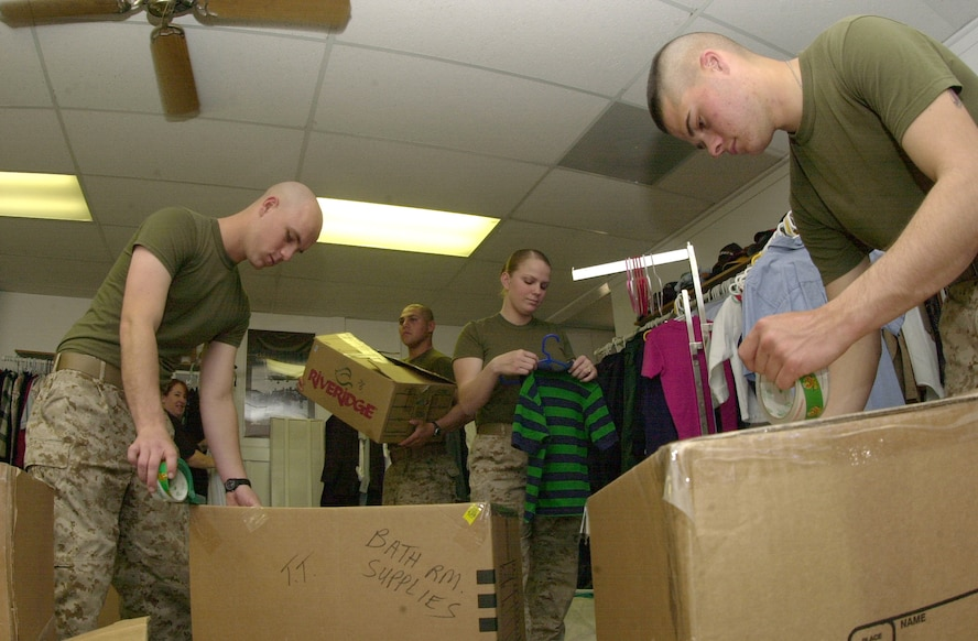 From left to right:  Marine Pfc. Rueben Johnson, Marine Pvt. Antonio Trejo (carrying box), Marine Pfc. Alison Wilson and Marine Pvt. Michael Brunett volunteered to pack up winter clothing items at SAMS Place Mar. 5 in order to make room for clothing items more suitable for the upcoming spring and summer seasons.
