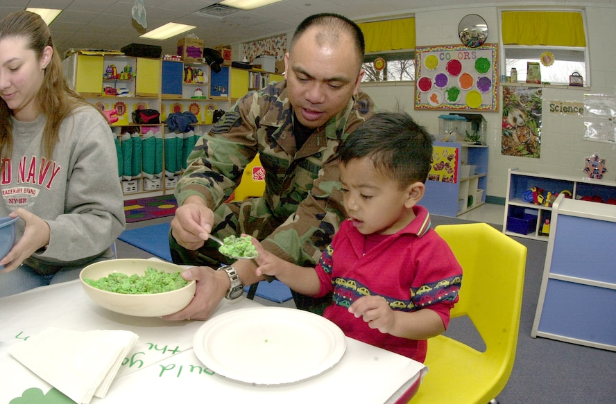 "Tech. Sgt. Al Cachola serves his 2-year-old son Daniel a spoon full of green eggs and ham Mar. 2 at the base Child Development Center. The CDC hosted the ""green"" event as a way of observing St. Patrick's Day, while encouraging parental involvement and education through reading."