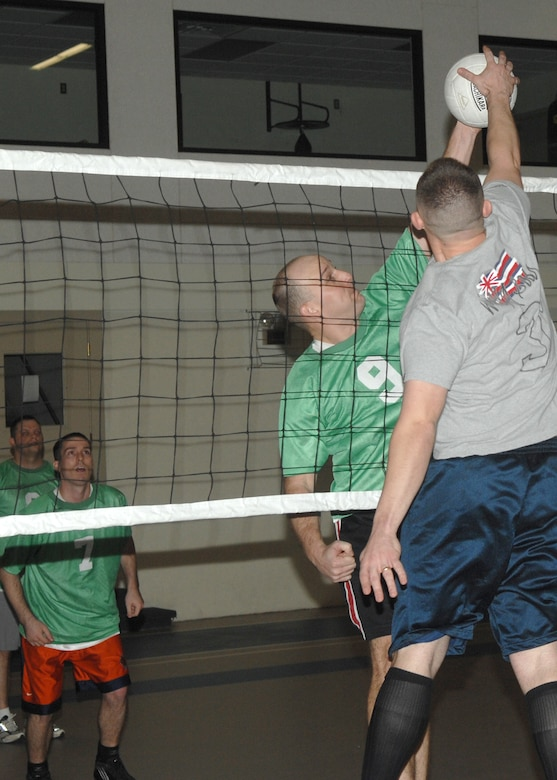 Number 9, Christopher Clark, a member of the 17th Communication Squadron Comm Batts base volleyball team, battles for possession of the ball with a defender from the 315 Rattlers Tuesday at the Carswell Field House during an intramural volleyball game. The 315 Rattlers won the games 25-19, 22-25 and 15-6.