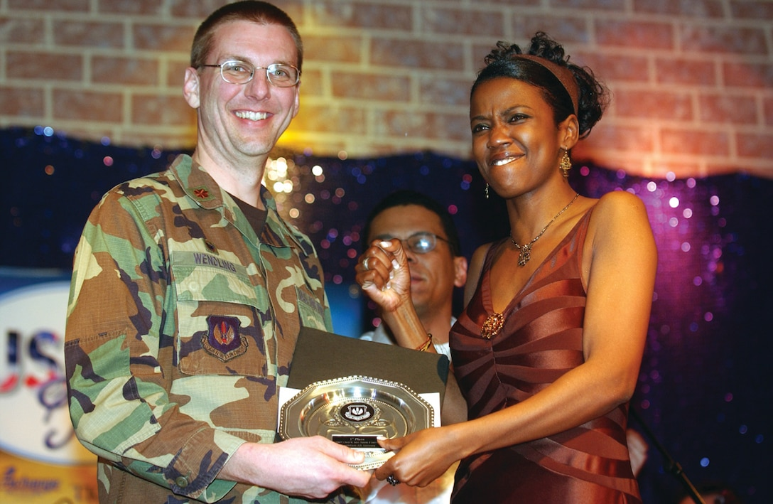 SPANGDAHLEM AIR BASE, GERMANY -- Capt. Stephanie Bankston, 52nd Medical Group, accepts the 1st place plaque from Maj. David Wendling, 52nd Services Squadron commander, after named the winner of the Spangdahlem Idol competition, March 2. Captain Bankston will moves on to the U.S. Air Forces in Europe level competition April 14. (US Air Force photo by/Senior Airman Josie Kemp)