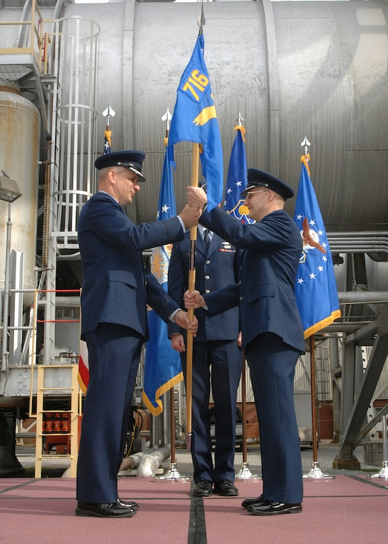 AEDC 704th Test Group Commander Col. Jeff Smith hands the 716th Test Squadron's command flag to Lt. Col. William 'Bill' Hack with the Propulsion Wind Tunnel facility's 16-foot transonic wind tunnel in the background March 12.