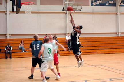 Steve Shelton, 437th Aircraft Maintenance Squadron, shoots the ball as Julio Reyes (right), 437th Services Squadron, Rich Etterling (center), SVS, and Kenneth Travis (left), AMXS, watch for the rebound during the basketball game March 13 at the fitness center.  AMXS defeated SVS 58-31.  (U.S. Air Force photo by Staff Sgt. Marie Cassetty)