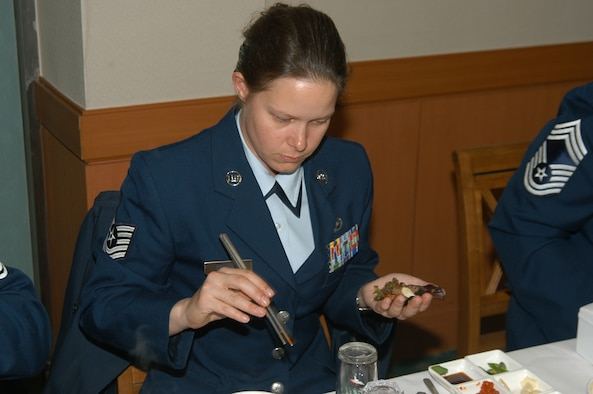 KUNSAN AIR BASE, Republic of Korea March 10, 2007 -- Tech. Sgt. Michelle Colburn learns the inner workings of chopsticks while dining at the Republic of Korea army NCO academy March 10. Five 8th Fighter Wing 'Wolf Pack' members, including Sgt. Colburn, have volunteered to teach up and coming ROK army NCOs conversational English as part of a new program between the academy and Kunsan. (Air Force photo/Senior Airman Stephen Collier)