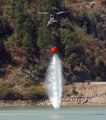 """A CH-47 Chinook drops water from the """"Bambi Bucket"""" system during a training mission March 15.  The 2,000-gallon bucket is designed to hang from the helicopter, collect water, and disperse the water at the touch of a button over a fire.  The training took place in small body of water along the Rio del Hombre, near the town of Zambrano, Honduras. (U.S. Air Force photo/Tech. Sgt. Sonny Cohrs)"""