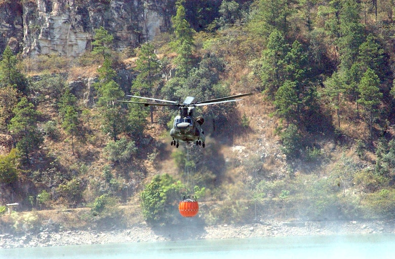 """A CH-47 Chinook collects water with a """"Bambi Bucket"""" system during a training mission March 15.  The 2,000-gallon bucket is designed to hang from the helicopter, collect water, and disperse the water at the touch of a button over a fire.  The training took place in small body of water along the Rio del Hombre, near the town of Zambrano, Honduras. (U.S. Air Force photo/Tech. Sgt. Sonny Cohrs)"""