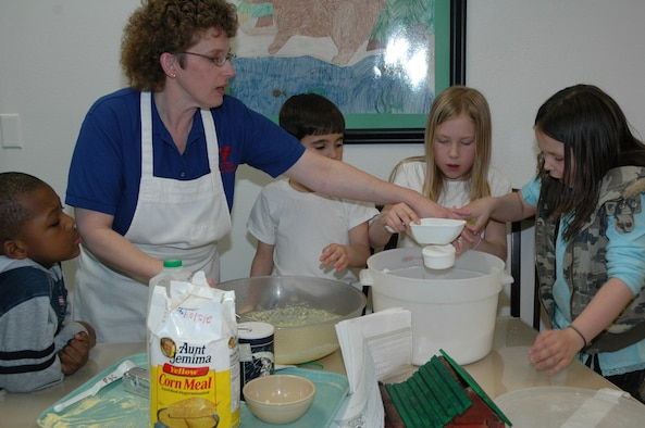 """""""Ms. Marjorie"""" Hahn is shown with Little Warriors (left to right) Jaylen, 6; Parker, 7; Reagan, 9; and Terryn, 8, during 4-H cooking class March 7 at the Youth Program Center. The children learned to make slapjacks."""