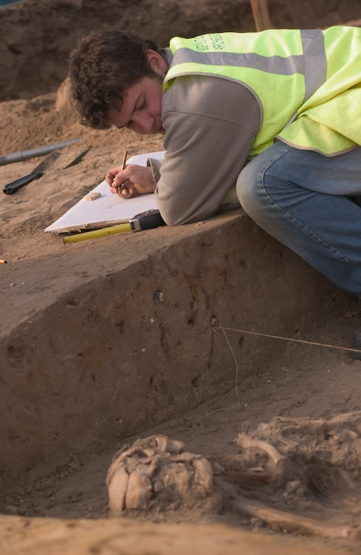 John Sims, an archeologist for Suffolk County Council, England, sketches a drawing March 14 of human remains prior to removing the bones for further study at the company's home office. The skeleton was found during an excavation of land where new base housing is planned to be constructed. It was estimated on site to be of 1st Century AD. Roman descent between 1,900 and 2,000 years old.  Mr. Sims has worked for Suffolk County Council for one and a half months, and the skeleton is his first significant find. (Air Force photo by Tech. Sgt. Tracy L. DeMarco)