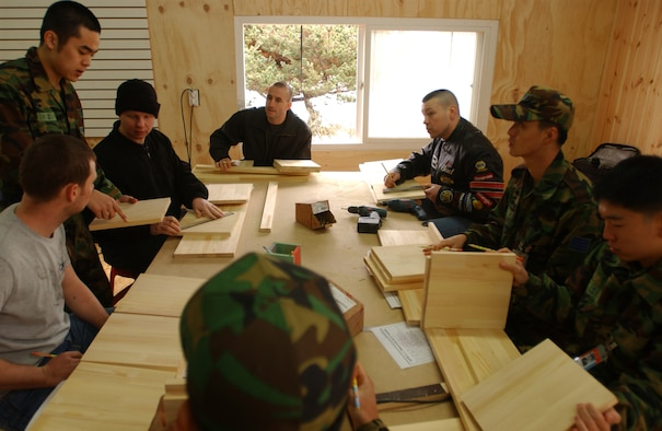 OSAN AIR BASE, Republic of Korea --  Senior Airman Kim, Jun-Yong, Republic of Korea Air Force public affairs office, helps members from the 51st Fighter Wing and 7th Air Force with a wood working project Saturday. The group went to the Wootdali Cultural Center near Osan at the invitation of the ROK Air Force Operations Command as part of the Good Neighbor Program. (U.S. Air Force photo by Airman Jason Epley)